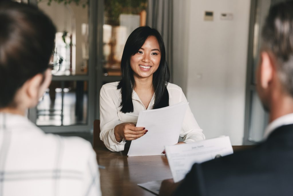 woman in a job interview with resume in her hand talking to two people