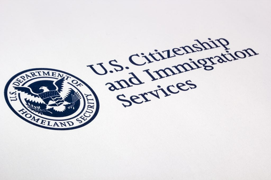 Logo of U.S. Citizenship and Immigration Services. Logo is dark blue and white