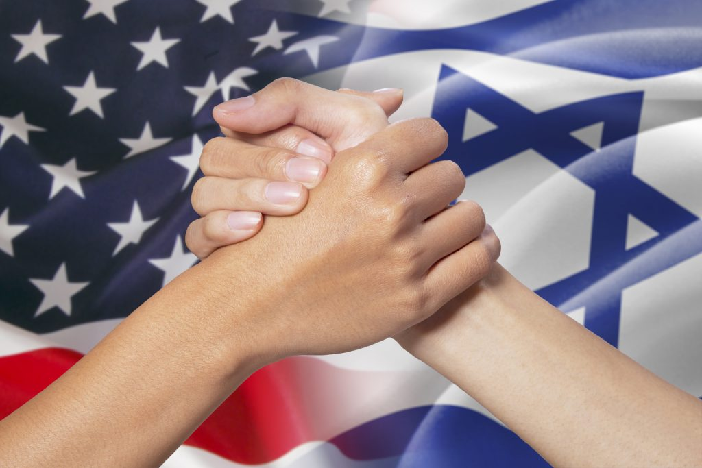 two women holding each other hands with the jewish and american flag in the background to symbolize two different coming together