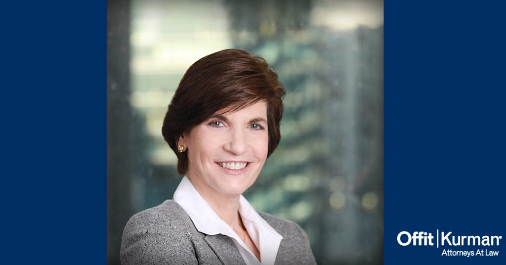 Professional headshot of Bettina Hindin, between 2 blue pillars with the Offit kurman Logo in the bottom left side of the picture