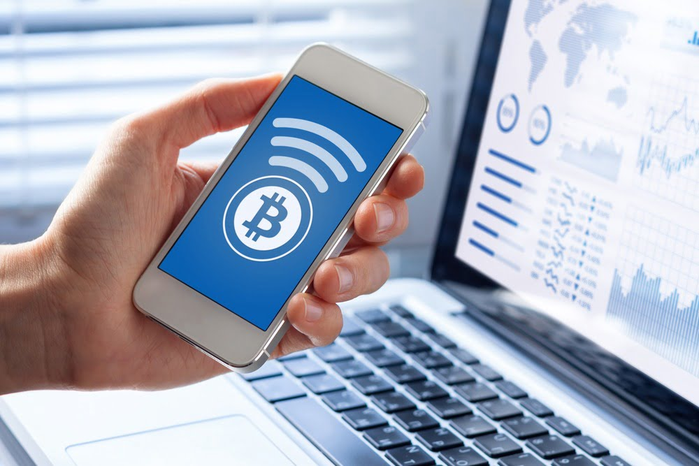 Man holding phone with picture of a bitcoin on it, holding phone over a laptop