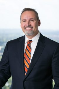 Picture of Mike Mercurio wearing a black jacket, white shirt, and a blue, light orange, and dark orange tie