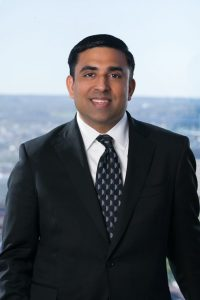 Picture of Rajiv Goel wearing a black suit, white shirt, and black with gray patterned tie