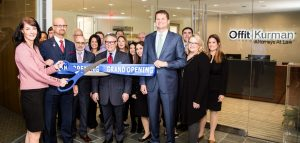 Picture of Tysons Corner Lawyers in front of their new office holding big blue scissors and cutting a grand opening sign