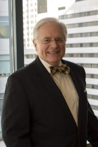 Picture of Thomas Hicks wearing a black jack, white blouse, and a black and yellow bowtie