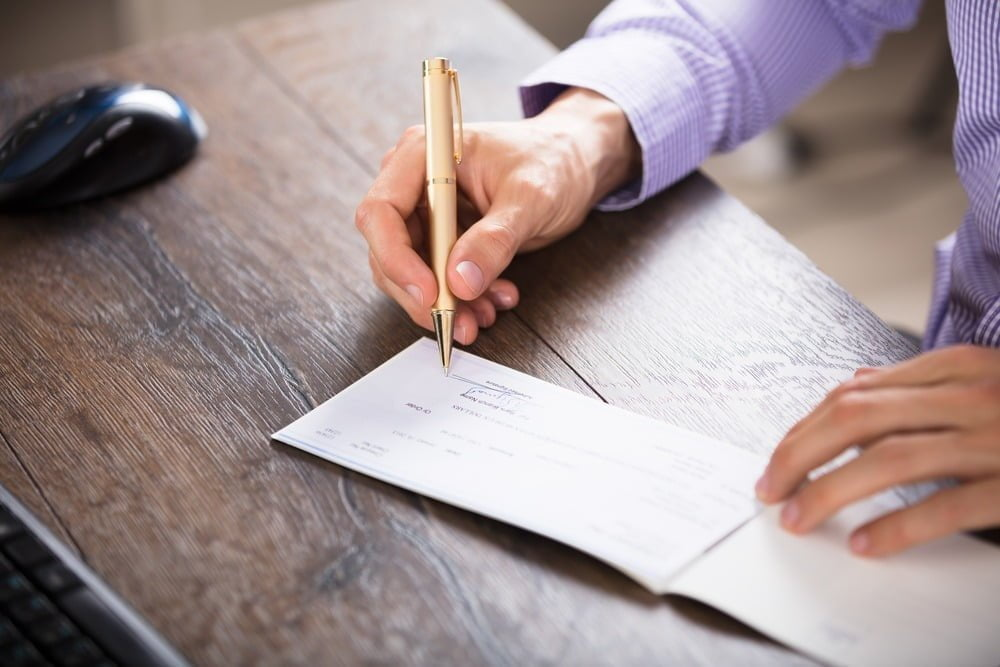 Man in purple button up shirt holding a pen and writing a check on a wooden desk