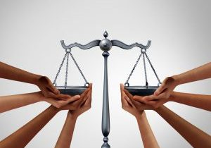 Multiple hands holding up both sides of the silver scales of justice.