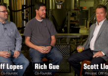 Video pic of Geoff Lopes and Rich Gue, Co-Founders of Hysteria Brewing Company interviewed by Scott Lloyd. 3 Men talking with each other and holding a glass filled with beer in their hands sitting in a distilling factory
