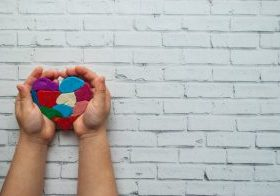 Child's,Hands,Holding,A,Multicolored,Heart,On,White,Background,With