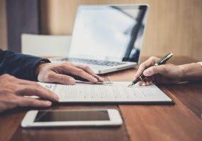 Sales,Manager,Filing,Keys,To,Customer,After,Signing,Rental,Lease