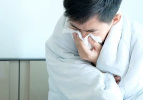 Sick man is flu, using a paper napkin and he have a runny nose. And he was covered in warm cloth.Health concept