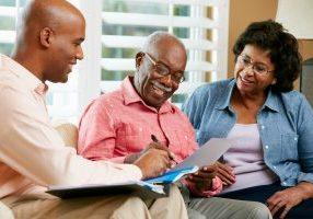 Financial,Advisor,Talking,To,Senior,Couple,At,Home