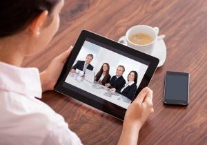 Woman looking at an ipad that has a pic of 4 people in a business meeting