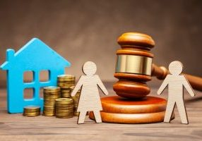 Divorce by law. Division of property after a divorce. The husband is trying to sue his wife for property under the law. A woman with a house and money, and a man with a hammer of a judge.