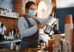 Beautiful Latin American Female Barista in Face Mask is Making a Cup of Cappuccino in Coffee Shop Bar. Social and Medical Health Restrictions Concept in a Loft-Style Cafe During Coronavirus Pandemic.
