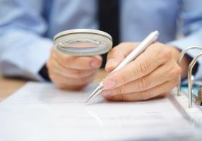 Businessman,Is,Analyzing,Through,Magnifying,Glass,Contract,And,Prices