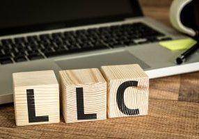 LLC (Limited Liability Company) written on a wooden cube in a office desk