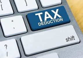 """Zoomed in view of a keyboard that shows a big blue key that reads """"TAX DEDUCTION"""""""
