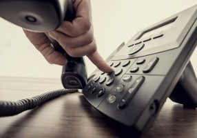 Closeup,Of,Male,Hand,Holding,Telephone,Receiver,And,Dialing,A