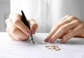 Woman signing marriage contract, closeup