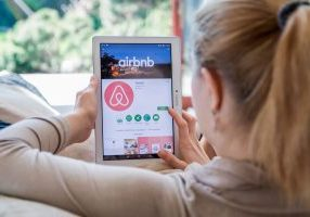 Airbnb on womans ipad making reservations in living room