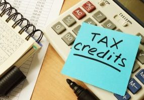 Memo sticky with words tax credits. place on a calculator