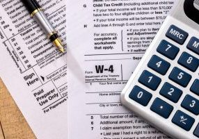 Close up image of a W-4 tax form and a calculator.