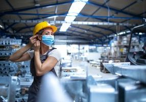 Shot,Of,Female,Factory,Worker,In,Uniform,And,Hardhat,Putting