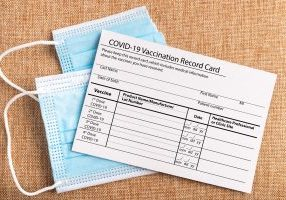 Coronavirus,Vaccination,Record,Card.,Protective,Mask,Divided,Into,Two,Parts.