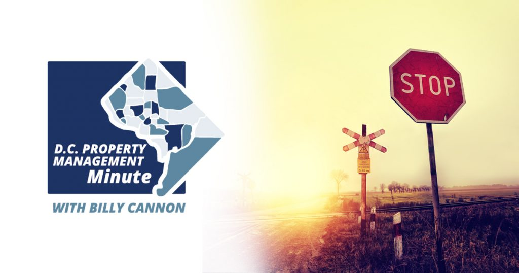 on left side of photo: D.C. Property Management MInute logo wit Billy Cannon. On right side of photo: Stop sign next to railroad track