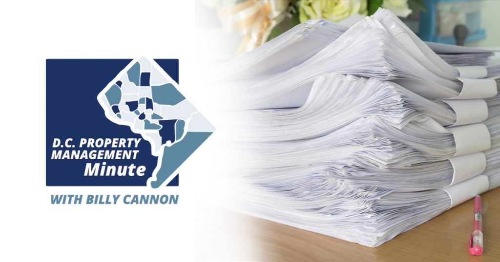 white and blue logo that reads: D.C. Property Management Minute with Billy cannon. Next to logo is a stack of paper on a table and a pink pen next to it