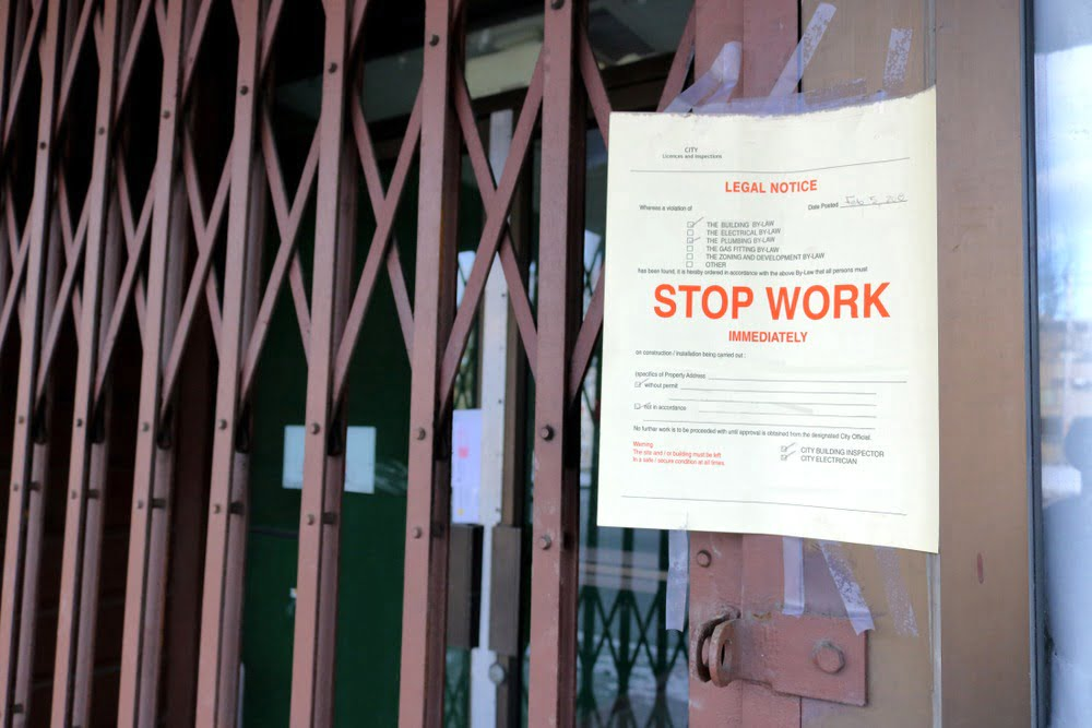 A notice has been posted in front of a building ordering the premises to stop work immediately.