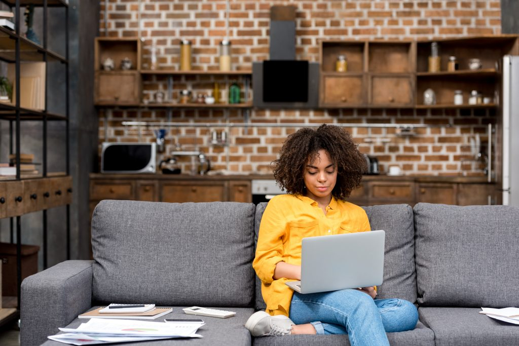young woman working working with laptop on couch