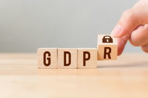 Hand flip wood cube block with word GDPR. Concept legal EU protect information general data protection regulation and sign key icon