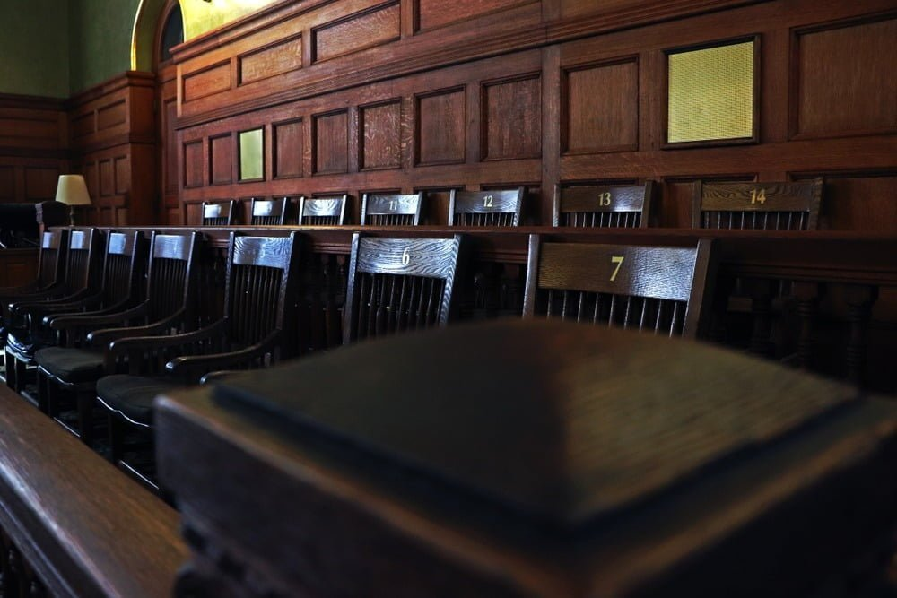 Angled photo of dark wood jury seats in a courtroom labeled numbers 1 through 14.