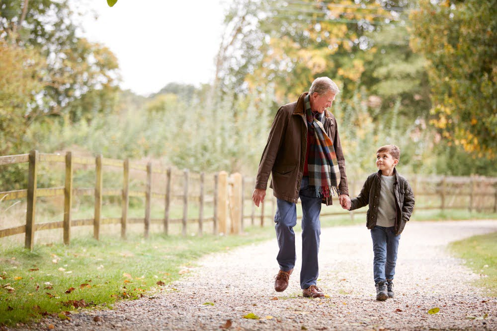 grandparent and child holding hands while walking down a gravel path in nature