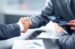 Two business men wearing suits shaking each others hands for a business deal