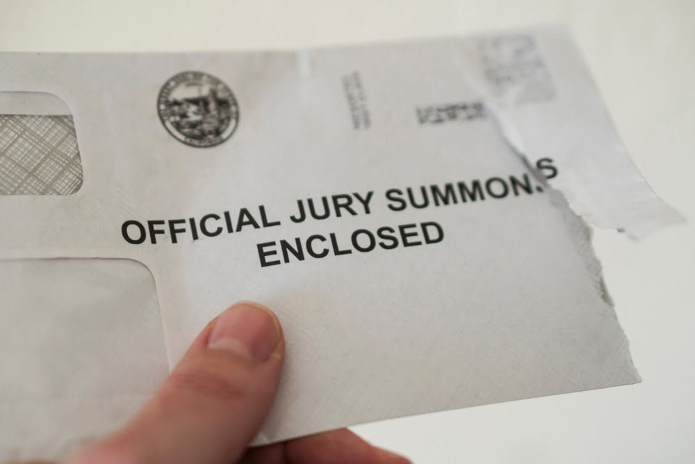 Closeup of open jury duty summons envelope, hand holding letter with white background, juror receiving notice. B