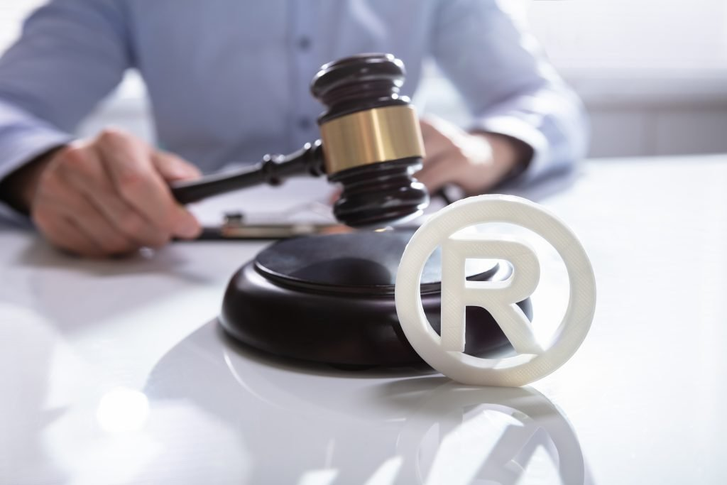 Close-up Of Judge Striking Mallet On Trademark Copyright Symbol A