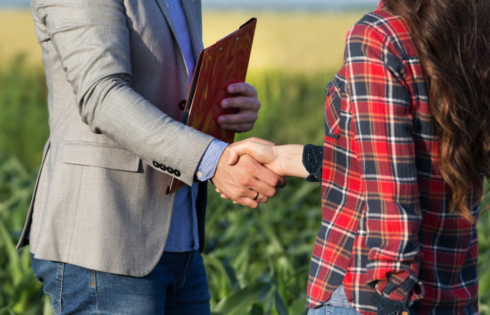 man shaking womans hand on sale of farm property