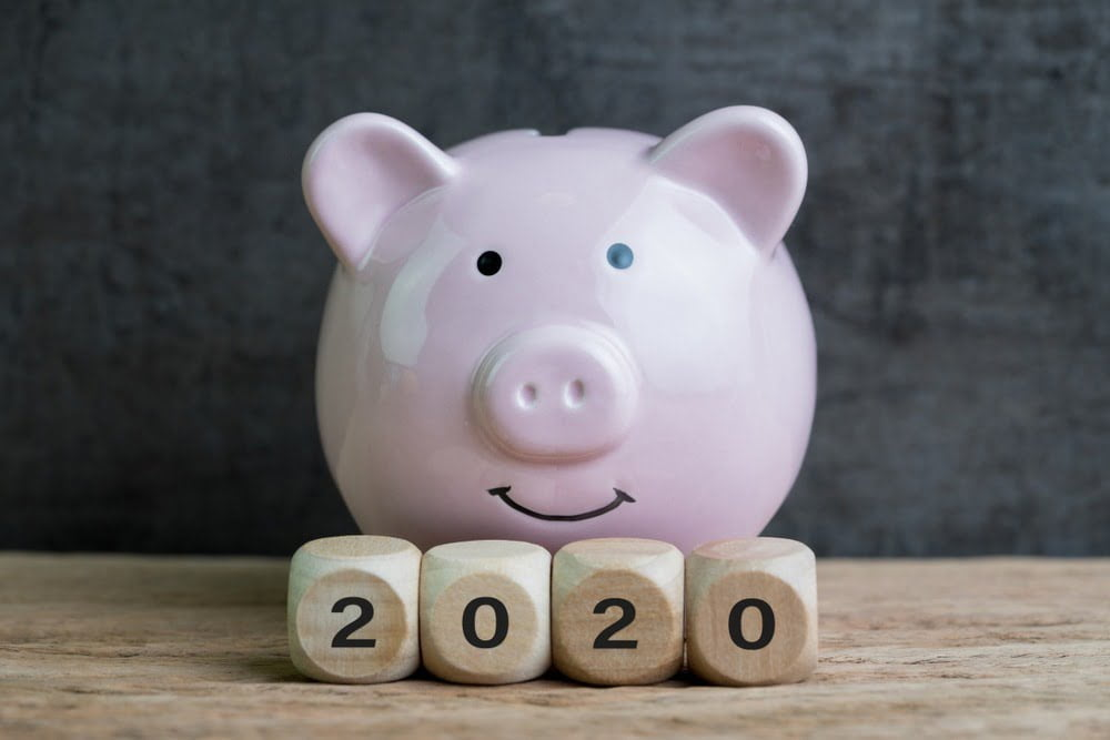 Pink piggy bank on a wooden table, with wooden blocks spelling out 2020.