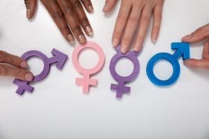 An Overhead View Of Multiethnic People Holding Different Type Of Gender Sign On White Table