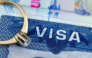 Engagement ring on top of blurred US entry visa sticker in a passport