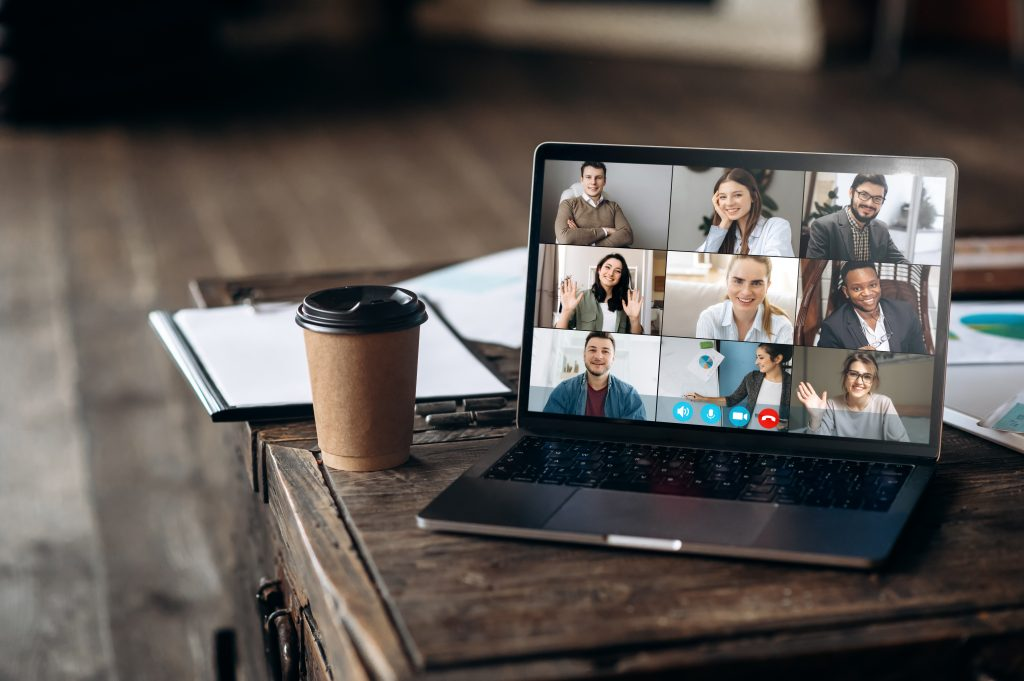 Virtual meeting online. Video conference by laptop. Online business meeting. On the laptop screen, people who gathered in a video conference to work on-line, near stands a cup of coffe