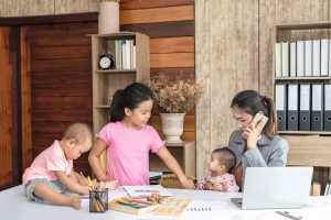 Busy woman trying to work while babysitting three kids. Young Asian mother on a call with three children playing around her . Working women with multitasking. R