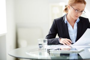 Young businesswoman sitting at workplace and reading paper in office