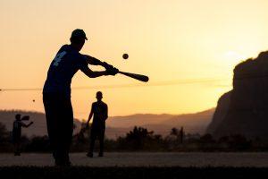 young boys play baseball swining a bat