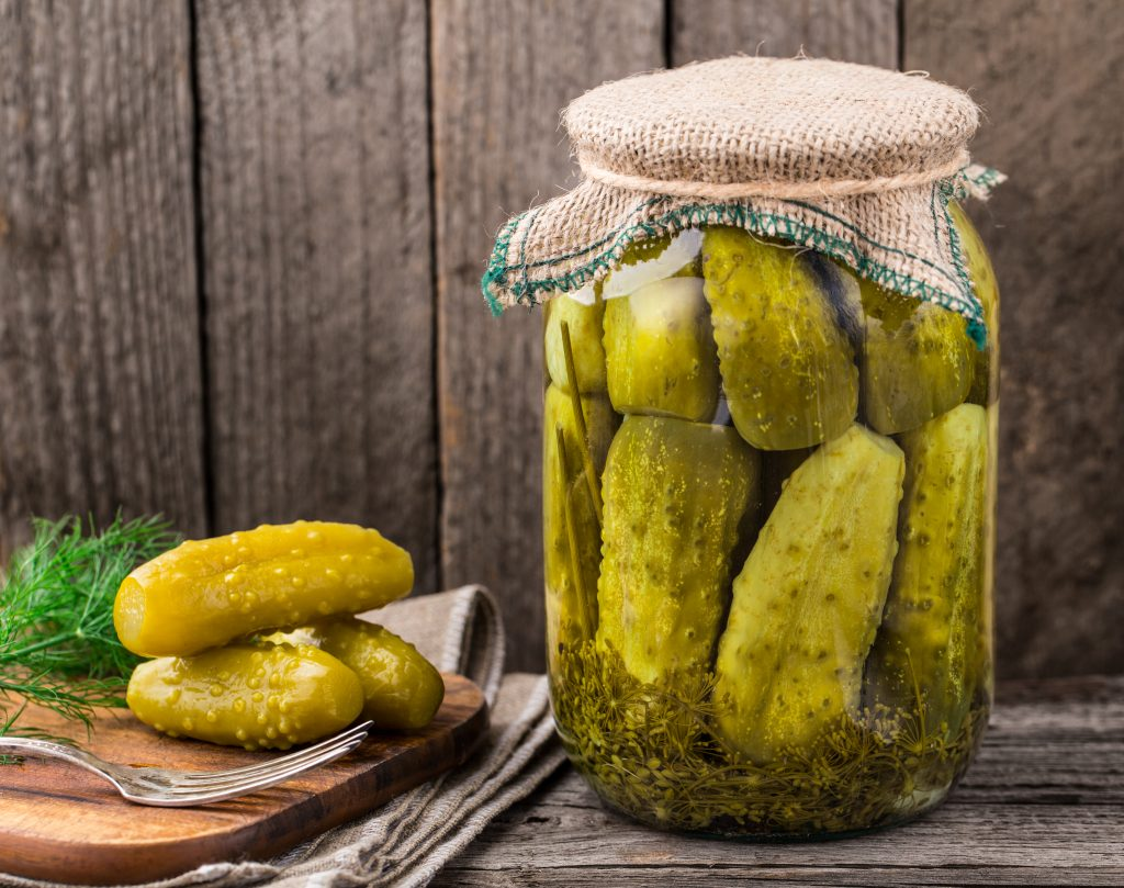 Jar of pickles with a burlap top and a wood cutting board with three pickles to the left.