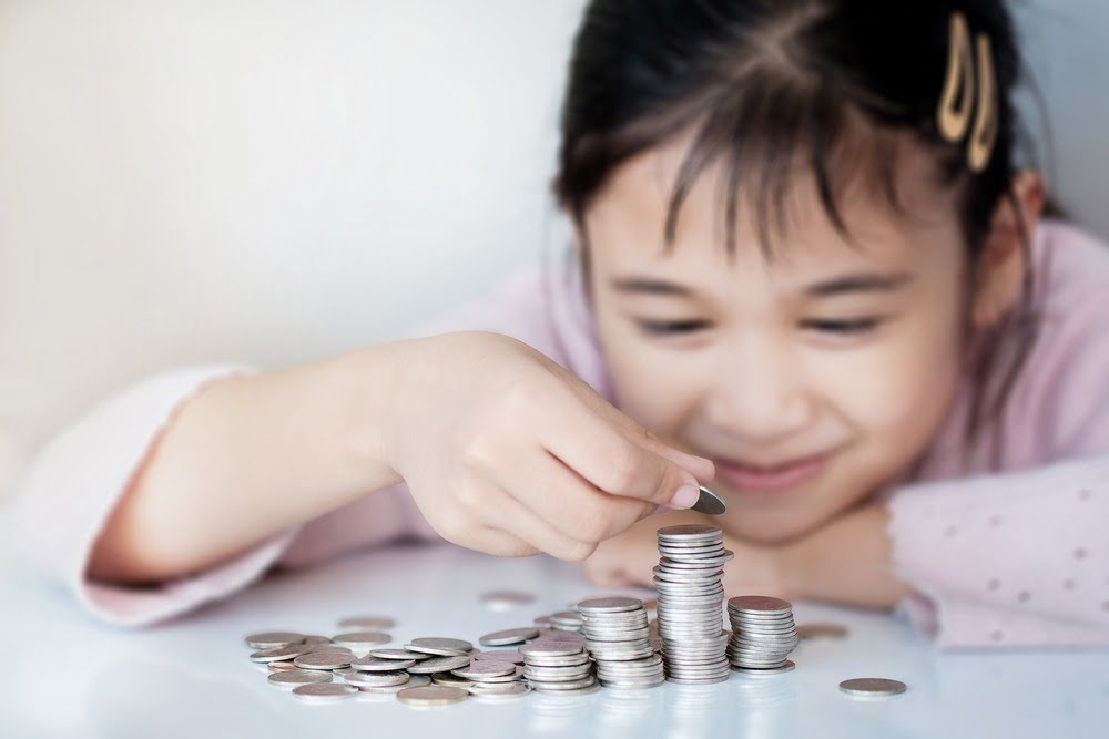 small female child smiling and counting up her savings and stacking coins.