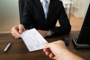 Man handing a business women a check